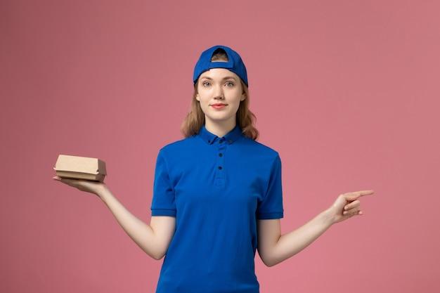 青いユニフォームとピンクの背景に小さな配達食品パッケージを保持している岬の正面図の女性の宅配便 無料写真