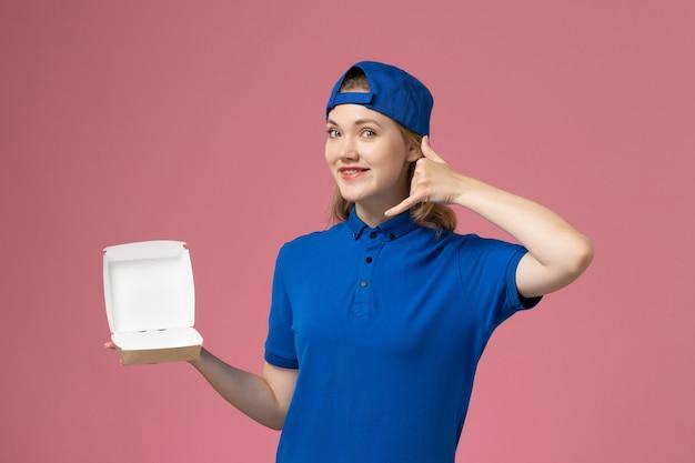 青い制服とケープの正面図の女性の宅配便ピンクの背景に小さな配達食品パッケージを保持している仕事配達制服サービスの従業員 無料写真