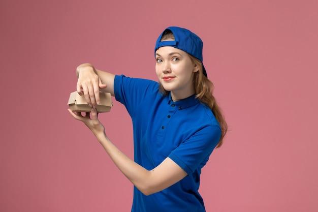ピンクの背景の配達仕事の制服サービス会社で小さな配達食品パッケージを保持している青い制服と岬の正面図の女性の宅配便 無料写真