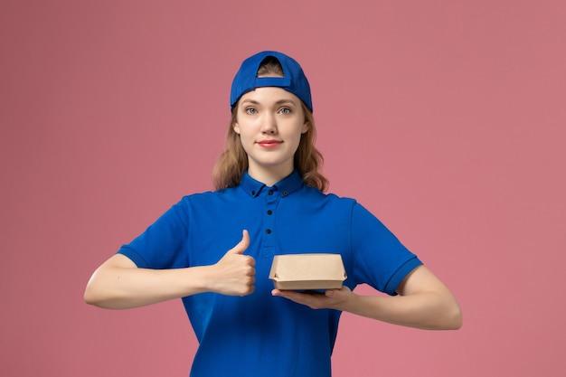 ピンクの背景に小さな配達食品パッケージを保持している青い制服と岬の正面図女性宅配便配達制服会社の仕事の女の子の仕事 無料写真