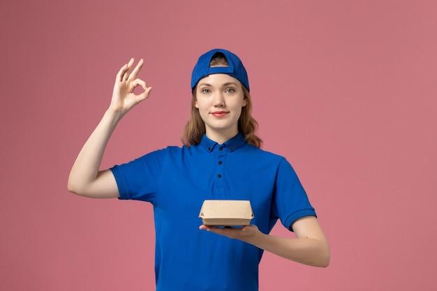 ピンクの背景に小さな配達食品パッケージを保持している青い制服と岬の正面図女性宅配便配達制服サービス会社の女の子 無料写真