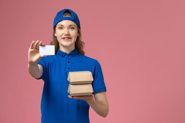 ピンクの背景のサービス配達従業員の仕事に小さな配達食品パッケージとカードを保持している青い制服ケープの正面図女性宅配便 無料写真
