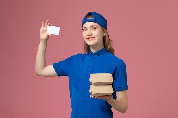 ピンクの背景サービス配達従業員に小さな配達食品パッケージとカードを保持している青い制服ケープの正面図女性宅配便 無料写真