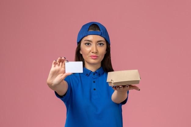 Вид спереди курьер-женщина в синей форменной накидке с маленькой посылкой с пластиковой картой на светло-розовой стене, работник службы доставки Бесплатные Фотографии