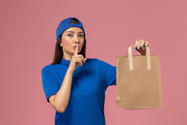 淡いピンクの壁で静かにするように求める紙の配達パッケージを保持している青い制服のケープの正面図の女性の宅配便、サービス従業員が配達 無料写真