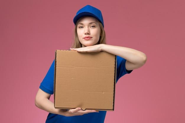 Вид спереди женщина-курьер в синей форме с коробкой для доставки еды на розовом фоне. Бесплатные Фотографии