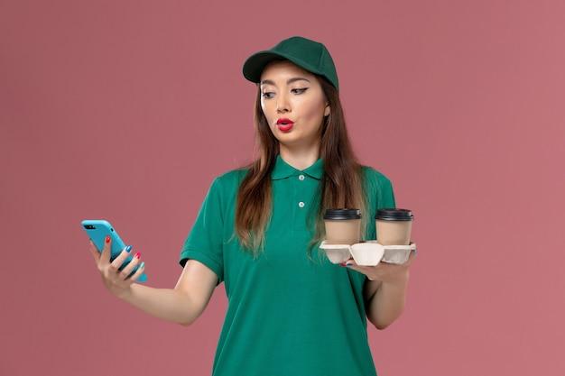 緑の制服を着た正面図の女性の宅配便と薄ピンクの壁のサービスの仕事の制服の配達で配達コーヒーカップと電話を保持している岬 無料写真