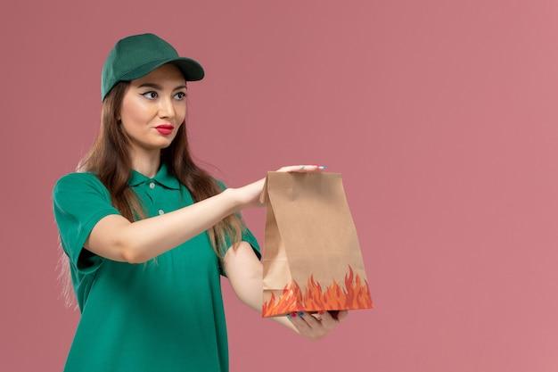 밝은 분홍색 벽 서비스 유니폼 배달에 종이 음식 패키지를 들고 녹색 제복을 입은 전면보기 여성 택배 무료 사진