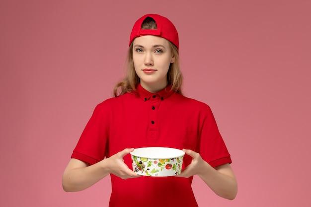 빨간색 유니폼과 밝은 분홍색 벽에 배달 그릇을 들고 케이프, 서비스 유니폼 배달 작업에 전면보기 여성 택배 무료 사진