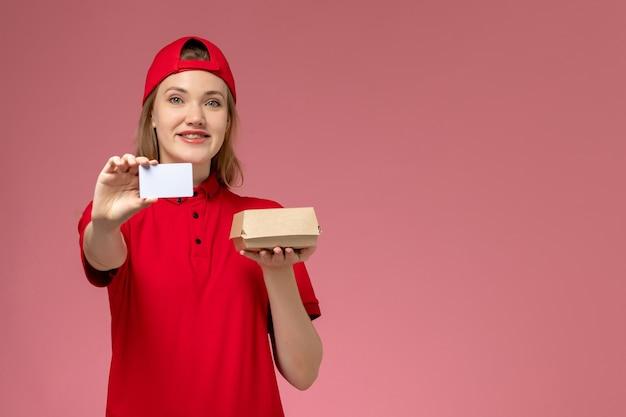 ピンクの壁に微笑んでいる白いプラスチックカードと小さな配達食品パッケージを保持している赤い制服と岬の正面図女性宅配便、サービスジョブ制服配達 無料写真