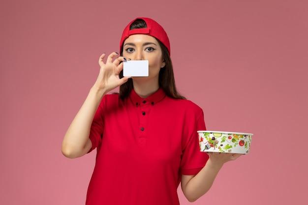淡いピンクの壁に配達ボウルと白いカードを手に持った赤い制服の岬の正面図の女性の宅配便、制服配達従業員の仕事 無料写真