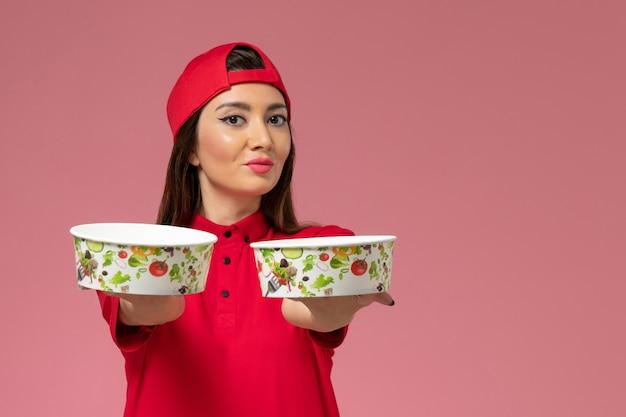 밝은 분홍색 벽, 서비스 배달 직원 노동자에 그녀의 손에 배달 그릇과 빨간색 유니폼 케이프에서 전면보기 여성 택배 무료 사진