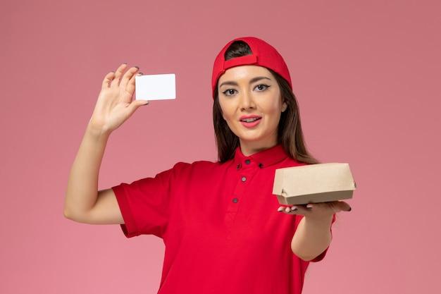 Курьер-женщина, вид спереди в красной униформе с небольшим пакетом продуктов для доставки и карточкой в руках на светло-розовой стене, служащий службы доставки Бесплатные Фотографии