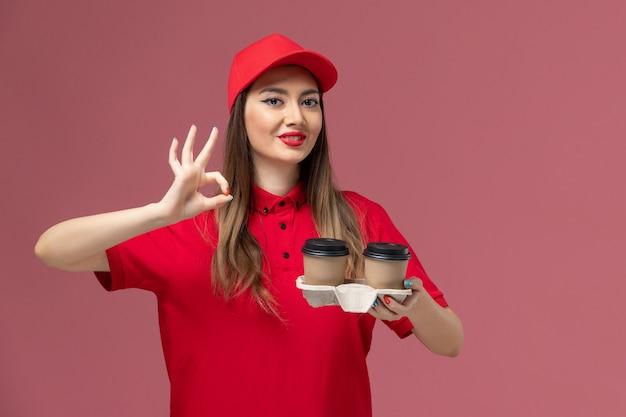 淡いピンクの背景に微笑んでいる茶色の配達コーヒーカップを保持している赤い制服の正面図女性宅配便サービス配達制服労働者の仕事の女性会社 無料写真
