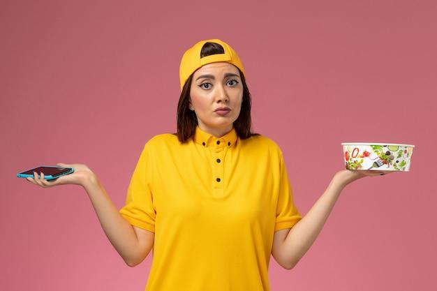 밝은 분홍색 벽 서비스 유니폼 배달에 배달 그릇과 스마트 폰을 들고 노란색 유니폼과 케이프의 전면보기 여성 택배 무료 사진