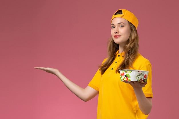노란색 유니폼과 케이프 핑크 벽 서비스 배달 작업 유니폼 작업자 소녀에 배달 그릇을 들고 전면보기 여성 택배 무료 사진