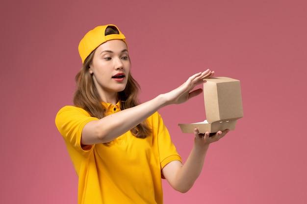 밝은 분홍색 벽 서비스 배달 유니폼 작업에 빈 작은 배달 음식 패키지를 들고 노란색 유니폼과 케이프에 전면보기 여성 택배 무료 사진
