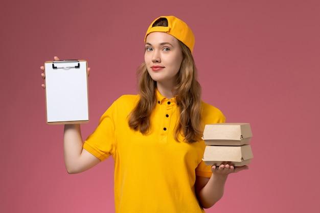 Вид спереди курьер-женщина в желтой форме и накидке с маленькими пакетами еды для доставки с блокнотом на розовой стене Бесплатные Фотографии