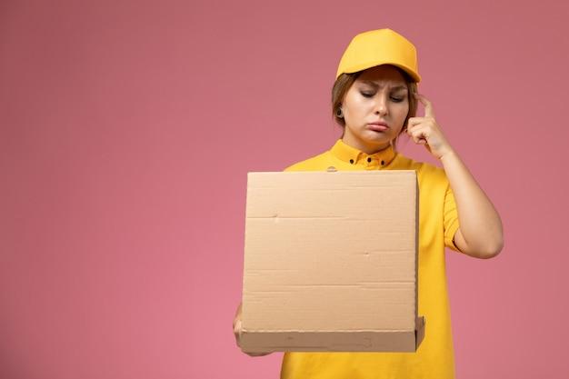 ピンクの机の上のフードボックスを保持し、開く黄色の制服黄色のケープの正面図女性宅配便制服配達女性の色 無料写真