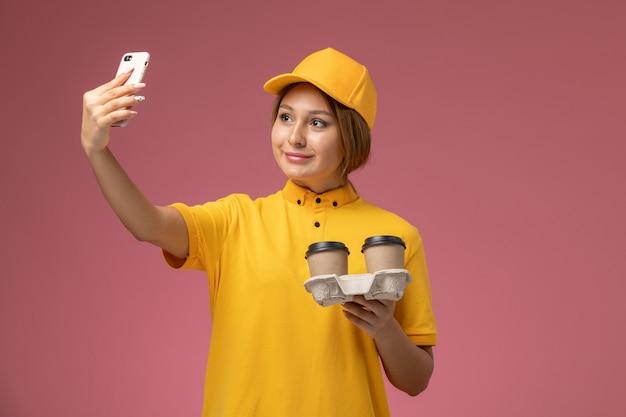 コーヒーカップを保持し、ピンクの背景に自分撮りをしている黄色の制服黄色の岬の正面図女性宅配便制服配達作業色の仕事 無料写真