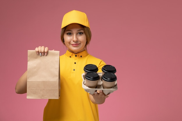 Вид спереди женщина-курьер в желтой униформе, желтой накидке, держащей кофейные чашки с едой на розовом фоне, цвет униформы доставки Бесплатные Фотографии