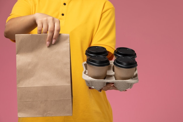 Вид спереди женщина-курьер в желтой униформе с желтым плащом держит пакет с едой и кофе на розовом фоне. Бесплатные Фотографии