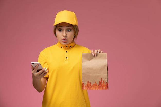 食品パッケージを保持し、ピンクの背景にスマートフォンを使用して黄色の制服黄色のケープで正面図の女性の宅配便 無料写真
