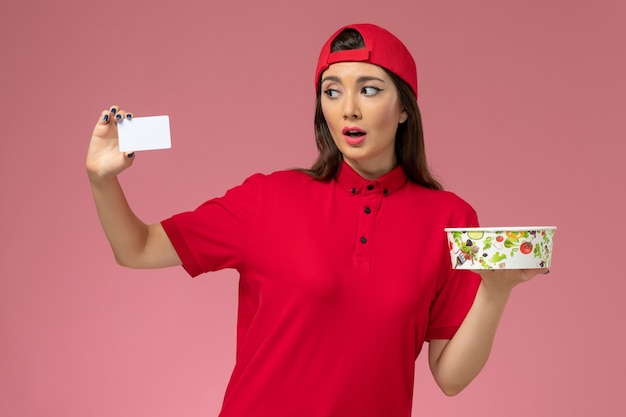 Front view female courier in red uniform cape with delivery bowl and white card on her hands on light pink wall, work job uniform delivery employee Free Photo