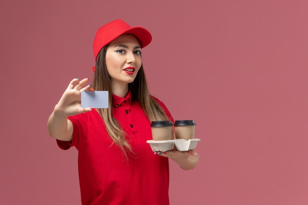Front view female courier in red uniform holding delivery coffee cups and card posing on pink background service job delivery uniform Free Photo