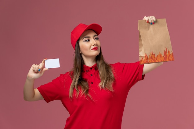 Front view female courier in red uniform holding white card and food package on the pink background service delivery uniform company Free Photo