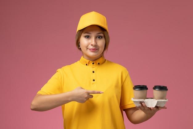 Corriere femminile di vista frontale in capo giallo uniforme giallo che tiene tazze di caffè di plastica con il sorriso sul lavoro di lavoro di consegna uniforme sfondo rosa Foto Gratuite