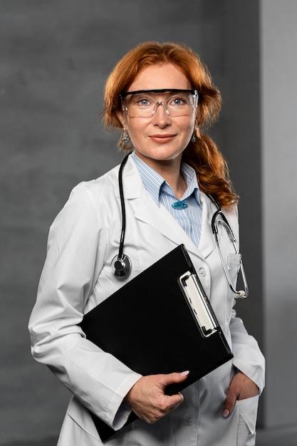 Vista frontale del medico femminile che tiene appunti e con gli occhiali Foto Gratuite