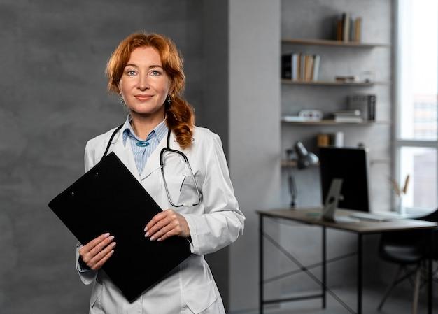 Vista frontale del medico femminile che tiene appunti con lo spazio della copia Foto Gratuite