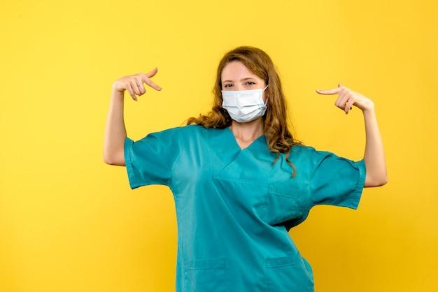 Вид спереди женщина-врач в маске на желтом пространстве Бесплатные Фотографии