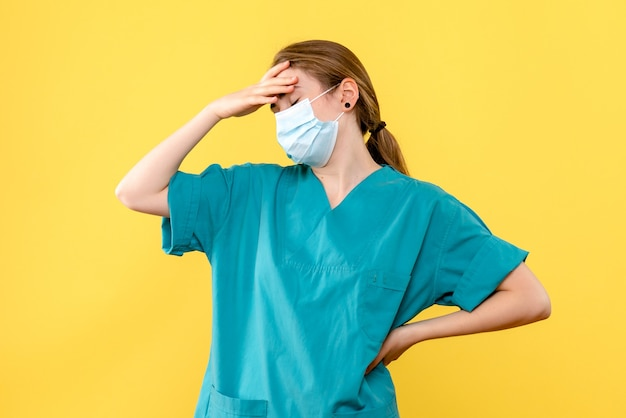 Front view female doctor in mask on yellow background virus health pandemic covid- Free Photo