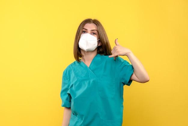 Вид спереди женщина-врач на желтом полу больницы пандемии вируса covid Бесплатные Фотографии