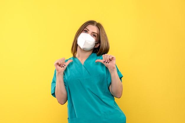 Вид спереди женщина-врач на желтом пространстве Бесплатные Фотографии