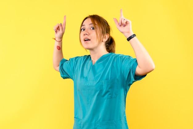 Medico femminile di vista frontale che alza le sue dita sullo spazio giallo Foto Gratuite