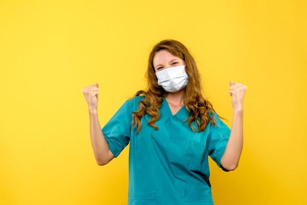 Вид спереди женщина-врач радуется в маске на желтом пространстве Бесплатные Фотографии