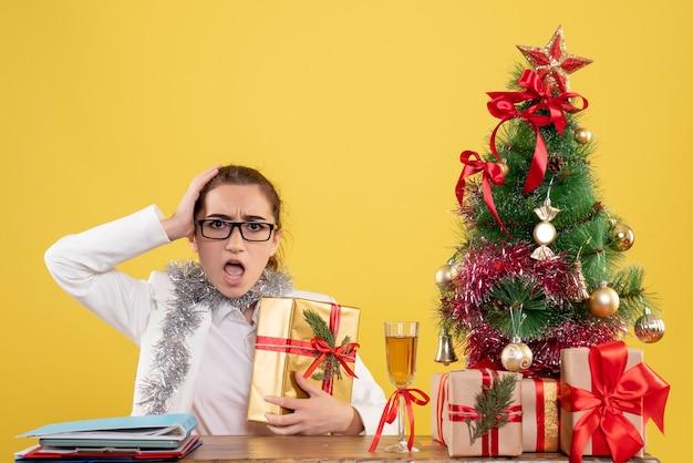 クリスマスプレゼントと黄色の背景にギフトを保持している木の周りに座っている正面図の女性医師 無料写真