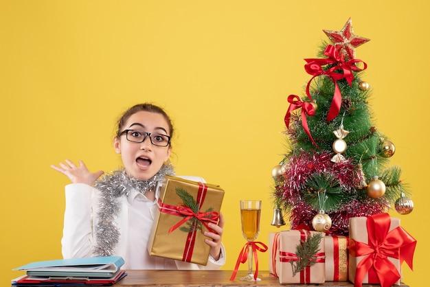クリスマスプレゼントと黄色の背景の木の周りに座っている正面図の女性医師 無料写真
