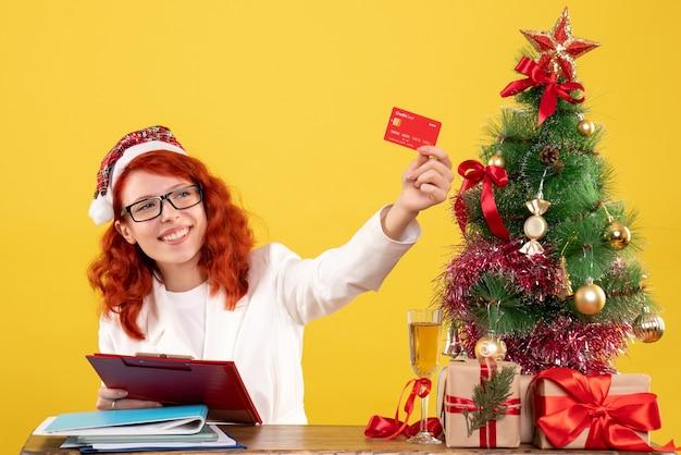 그녀의 테이블 뒤에 앉아 크리스마스 트리와 선물 상자와 노란색 배경에 은행 카드를 들고 전면보기 여성 의사 무료 사진