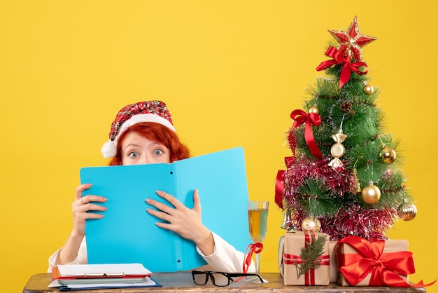 クリスマスツリーとギフトボックスと黄色の背景のドキュメントを読んでテーブルの後ろに座っている正面図の女性医師 無料写真