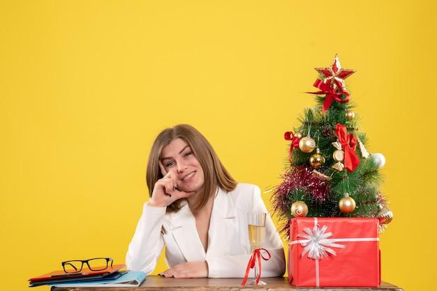 크리스마스 트리와 선물 상자와 노란색 배경에 그녀의 테이블 앞에 앉아 전면보기 여성 의사 무료 사진
