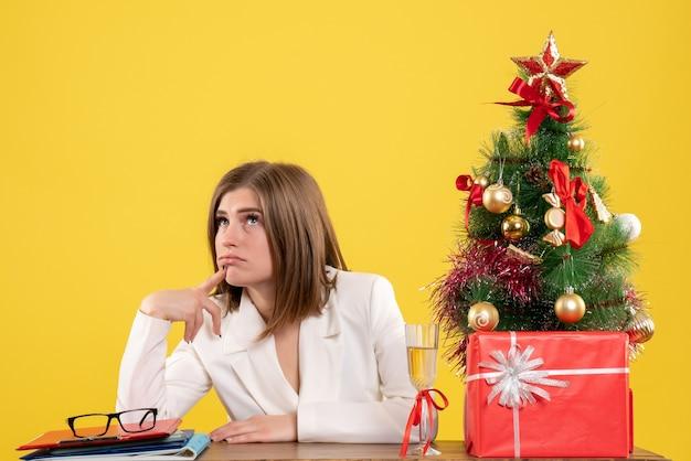 크리스마스 트리와 선물 상자와 노란색 배경에 생각 그녀의 테이블 앞에 앉아 전면보기 여성 의사 무료 사진
