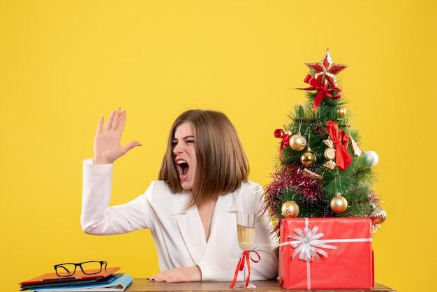 크리스마스 트리와 선물 상자와 노란색 배경에 테이블 앞에 앉아 전면보기 여성 의사 무료 사진