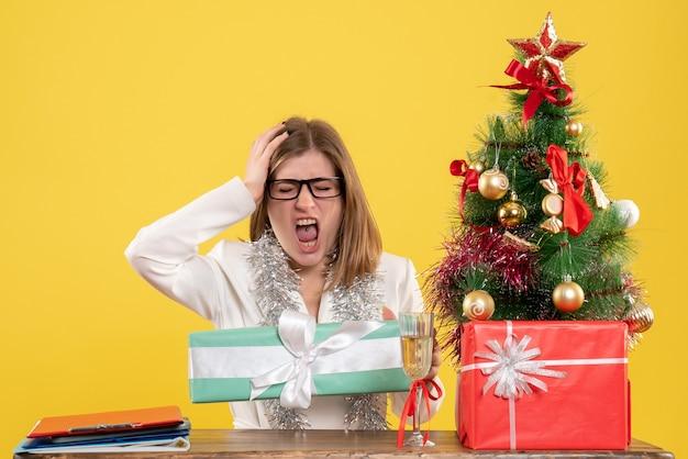 黄色の背景にプレゼントとクリスマスツリーとテーブルの前に座っている正面図の女性医師 無料写真