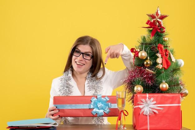 크리스마스 트리 및 선물 상자와 노란색 배경에 선물 및 트리 테이블 앞에 앉아 전면보기 여성 의사 무료 사진