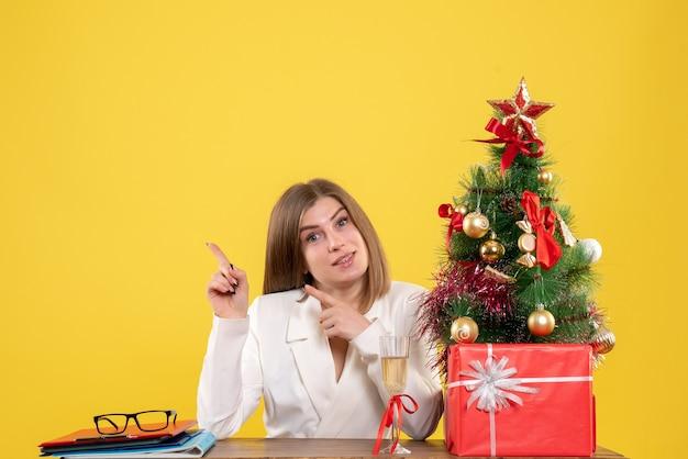 크리스마스 선물 테이블 앞에 앉아 전면보기 여성 의사와 노란색 배경에 나무 무료 사진