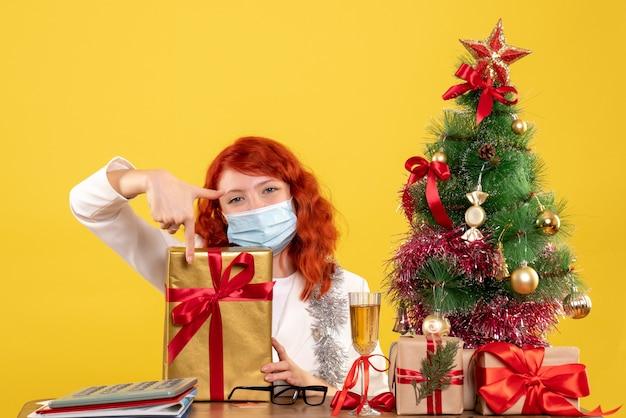 크리스마스 트리와 선물 상자와 노란색 배경에 크리스마스 선물 및 트리 마스크에 앉아 전면보기 여성 의사 무료 사진